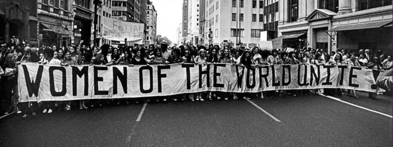 Women holding a Women of the World Unite banner